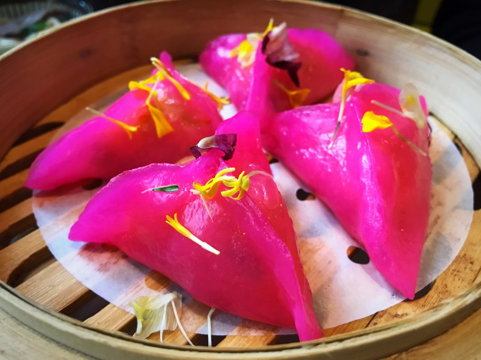 Another vibrant dish on Jingle Bao's menu is the crystal shrimp dumplings. Haw gao is shaped into a bright pink dumpling wrap and sprinkled with edible yellow flowers.