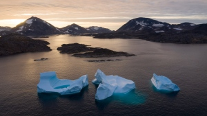 In this Aug. 16, 2019, file photo, large icebergs float away as the sun rises near Kulusuk, Greenland. (AP Photo/Felipe Dana, File)