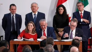 Deputy Prime Minister of Canada Chrystia Freeland, left, Mexico's top trade negotiator Jesus Seade, center, and U.S. Trade Representative Robert Lighthizer, sign an update to the North American Free Trade Agreement, at the national palace in Mexico City, Tuesday, Dec. 10. 2019. Observing from behind are Mexico's Treasury Secretary Arturo Herrera, left, Mexico's President Andres Manuel Lopez Obrador, second left, Mexico's Labor Secretary Maria Alcade, third left, and The President of the Mexican Senate Ricardo Monreal. (AP Photo/Marco Ugarte)