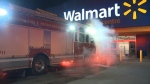 A fire truck is parked metres from the front doors of a Walmart store in north Regina on Dec. 10, 2019.