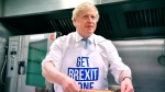 Britain's Prime Minister Boris Johnson prepares a pie at the Red Olive catering company while on the campaign trail, in Derby, England, Wednesday, Dec. 11, 2019. (Ben Stansall/Pool Photo via AP)