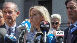 In this Aug. 27, 2019, photo, Virginia Giuffre, center, who says she was trafficked by sex offender Jeffrey Epstein, holds a news conference outside a Manhattan court where sexual assault claimants invited by a judge addressed a hearing following Epstein's jailhouse death in New York. (AP Photo/Bebeto Matthews)