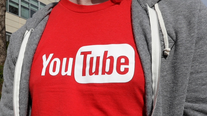 This April 4, 2018, file photo shows a YouTube logo on a t-shirt worn by a person near a YouTube office building in San Bruno, Calif. (AP Photo/Jeff Chiu, File)