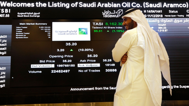 A Saudi stock market official smiles as he watches the stock market screen displaying Saudi Arabia's state-owned oil company Aramco after the debut of Aramco's initial public offering (IPO) on the Riyadh's stock market in Riyadh, Saudi Arabia, Wednesday, Dec. 11, 2019. (AP Photo/Amr Nabil)