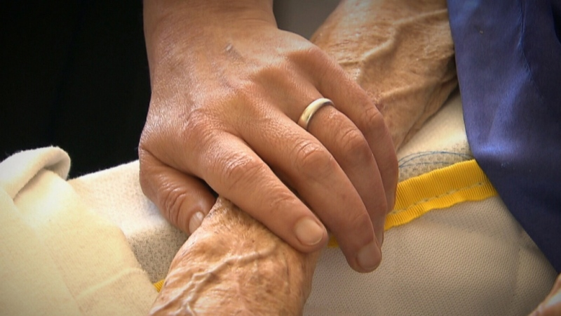 A person holds a senior's hand in this file photo.