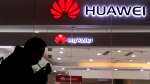 A man lights a cigarette outside a Huawei retail shop in Beijing Thursday, Dec. 6, 2018. (AP / Ng Han Guan)