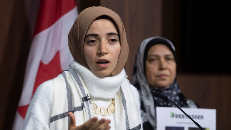 Safaa Eleshmawy (right), wife of Yasser Albaz, currently detained in Egypt, looks on as his daughter Amal Ahmed holds up a petition for his release during a news conference on Dec. 11, 2019 in Ottawa. THE CANADIAN PRESS/Adrian Wyld