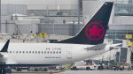 "An Air Canada Boeing 737 Max 8 aircraft is shown next to a gate at Trudeau Airport in Montreal on March 13, 2019. Transport Minister Marc Garneau says he has spoken with Air Canada about problems continuing to plague its new booking system, but that his department ""cannot do anything."" THE CANADIAN PRESS/Graham Hughes"