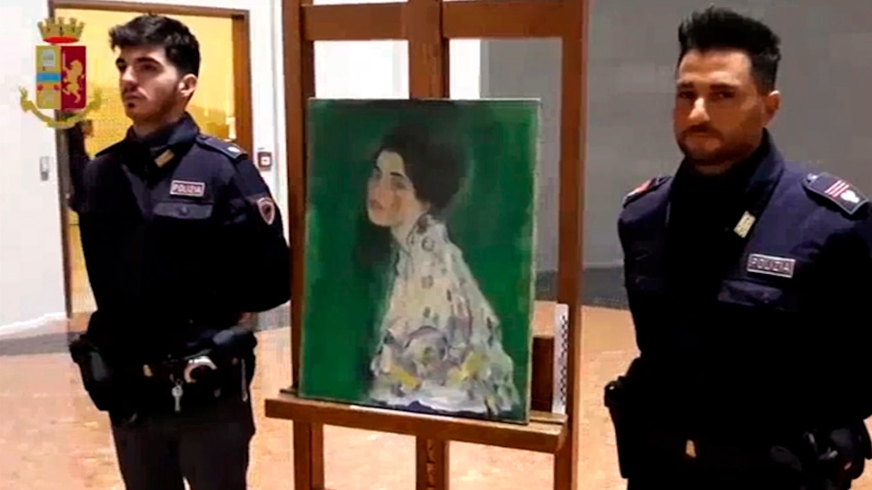 This image taken from a video distributed Wednesday, Dec. 11, 2019 by Italian police shows two police officers standing next to a painting which was found inside a gallery's walls, in Piacenza, northern Italy. (Italian Police via AP)