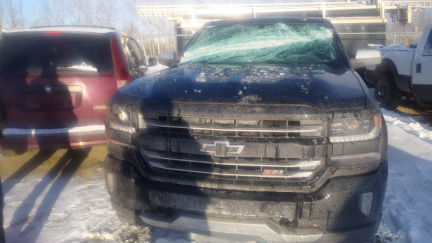 An out-of-control tire slammed into a lightpost which crashed down on this Chevy truck.