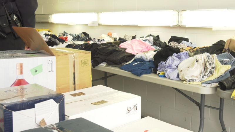 Boxes of booze and piles of designer clothes, all allegedly stolen, are seen at a Vancouver police news conference on Dec. 11, 2019.