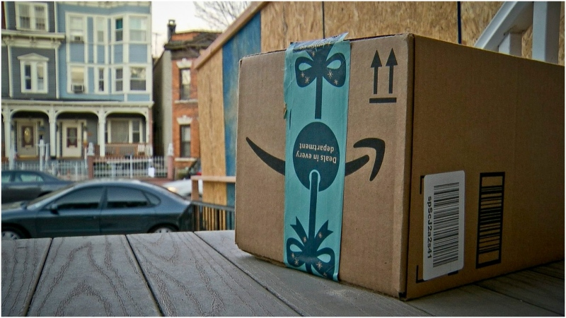 FILE - This Dec. 11, 2018 file photo shows an Amazon package containing a GPS tracker on the porch of a Jersey City, N.J. residence after its delivery. News of an alleged Amazon theft ring involving contract delivery drivers is unlikely to make a dent in the online shopping giant's massive business. But it may make people more wary of letting deliveries into their house when they aren't there _ a nascent project from both Amazon and Walmart. (AP Photo/Robert Bumsted)