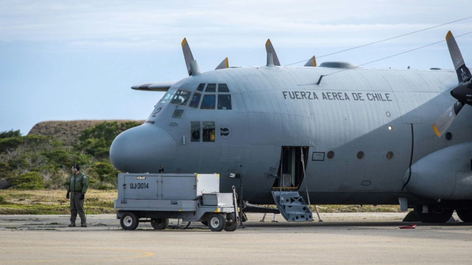 A man stands next to a C-130 plane that returned to Punta Arenas, Chile, from a search of the Drake Passage for a missing Air Force plane with 38 people aboard. (AFP)