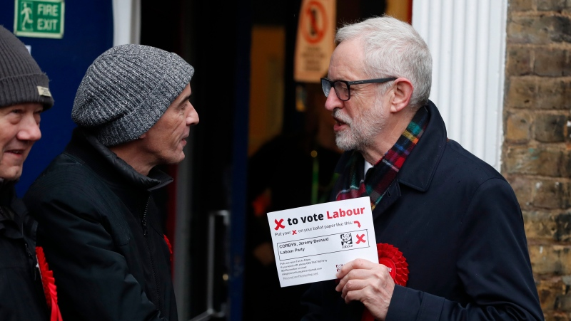 British opposition Labour Party leader Jeremy Corbyn, right, shakes hands with a supporter, after casting his vote in the general election, in Islington, London, England, Thursday, Dec. 12, 2019. (AP Photo/Thanassis Stavrakis)