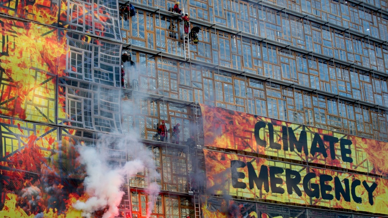 Climate activists send off smoke flares from behind a banner on the Europa building during a climate demonstration outside an EU summit meeting in Brussels, Thursday, Dec. 12, 2019. (AP Photo/Virginia Mayo)