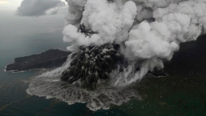 Plumes rise from Mount Anak Krakatau as it erupts in the Java Strait, Indonesia on Sunday, Dec. 23, 2018. (Nurul Hidayat/Bisnis Indonesia via AP)