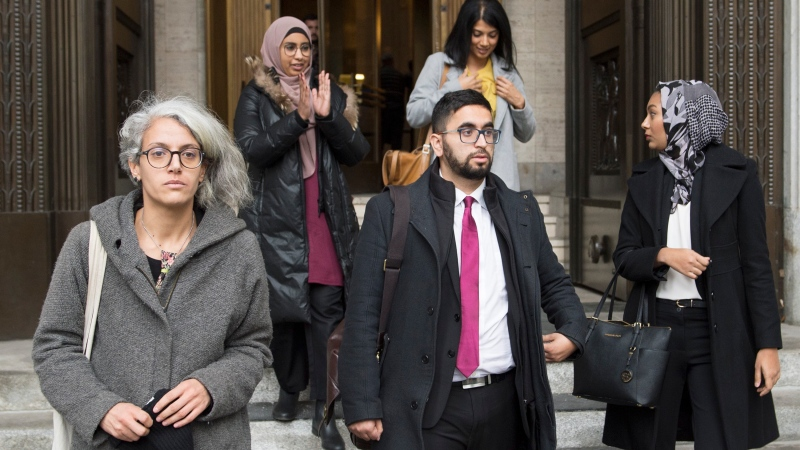 Members of the National Council of Muslims Mustafa Farooq, centre, and Bochra Manai, left, alongside supporters leave the Quebec Court of Appeal in Montreal, Tuesday, Nov. 26, 2019, where they are challenging Quebec's Bill 21. THE CANADIAN PRESS/Graham Hughes
