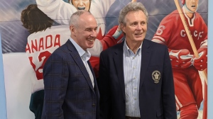 Ron MacLean, left, and Paul Henderson, right, pose in front of a Smilezone mural in Goderich, Ont. on Thursday, Dec. 12, 2019. (Joel Merritt / CTV London)