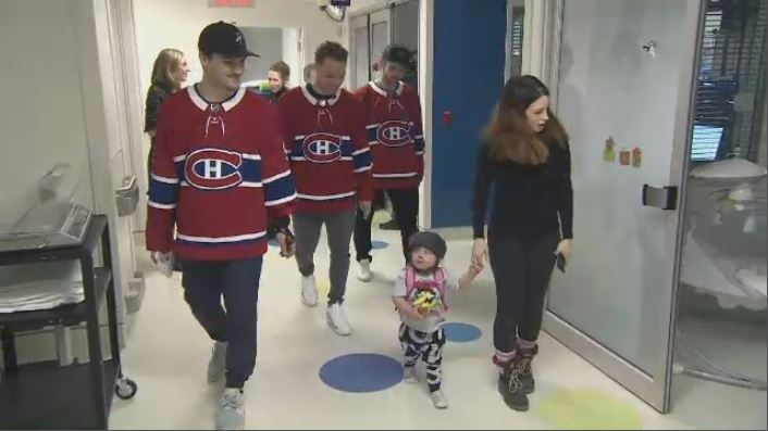 Montreal Canadiens players walk alongside a sick kid in the Montreal Children's hospital on Dec. 12, 2019.