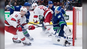 Vancouver Canucks goalie Jacob Markstrom, right, of Sweden, stops Carolina Hurricanes' Warren Foegele (13) during the third period of an NHL hockey game in Vancouver, on Thursday December 12, 2019. THE CANADIAN PRESS/Darryl Dyck