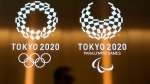 In this June 11, 2019, file photo, a man walks past the logos of the Tokyo 2020 Paralympics and Olympics in Tokyo.  (AP Photo/Jae C. Hong, File)