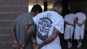 In this October file photo, suspected gang members are brought in handcuffed to each other, to the hearing room of the Isidro Menendez Judicial Center in San Salvador, El Salvador, Thursday, Oct. 10, 2019. (AP Photo/Salvador Melendez)