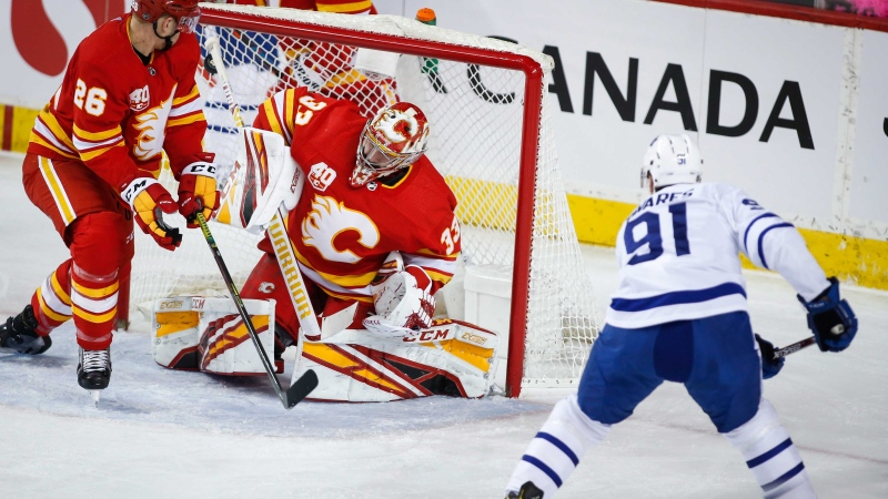 Toronto Maple Leafs' John Tavares, right, scores on Calgary Flames goalie David Rittich, centre, as Michael Stone looks on during first period NHL hockey action in Calgary, Thursday, Dec. 12, 2019.THE CANADIAN PRESS/Jeff McIntosh
