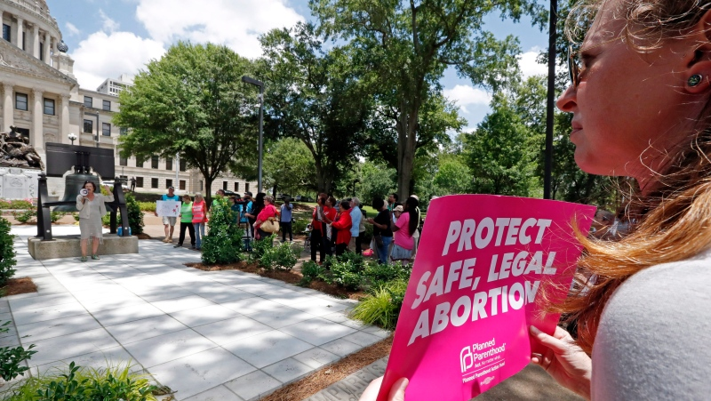In this file photo, an abortion rights advocate holds signage at the Capitol in Jackson, Miss., voicing her opposition to state legislatures passing abortion bans that prohibit most abortions once a fetal heartbeat can be detected, Tuesday, May 21, 2019. (AP Photo/Rogelio V. Solis)