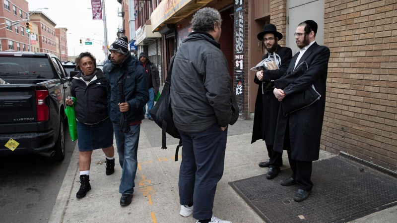 A passerby, center, stops to talk with two Jewish men, Friday, Dec. 13, 2019 in Jersey City, N.J. close to the site where multiple people and two gunmen were shot on Tuesday. (AP Photo/Mark Lennihan)