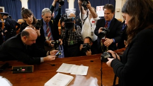 In this Dec. 13, 2019, photo, members of the press view the roll call vote recorded by the clerk after the House Judiciary Committee approved the articles of impeachment against U.S. President Donald Trump on Capitol Hill in Washington. (AP Photo/Patrick Semansky)