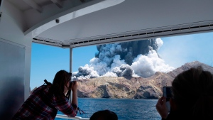 In this Dec. 9, 2019, file photo provided by Michael Schade, tourists on a boat look at the eruption of the volcano on White Island, New Zealand. (Michael Schade via AP)