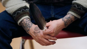 Ryan Beardy, former gang member and Healing Together founder, holds an eagle feather as he speaks during a meeting of Healing Together in Thunderbird House in downtown Winnipeg, Sunday, Dec. 8, 2019. THE CANADIAN PRESS/John Woods