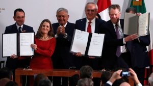 Mexico's Treasury Secretary Arturo Herrera, left, Deputy Prime Minister of Canada Chrystia Freeland, second left, Mexico's President Andres Manuel Lopez Obrador, center, Mexico's top trade negotiator Jesus Seade, second right, and U.S. Trade Representative Robert Lighthizer, hold the documents after signing and update to the North American Free Trade Agreement, at the national palace in Mexico City, Tuesday, Dec. 10. 2019. (AP Photo/Marco Ugarte)