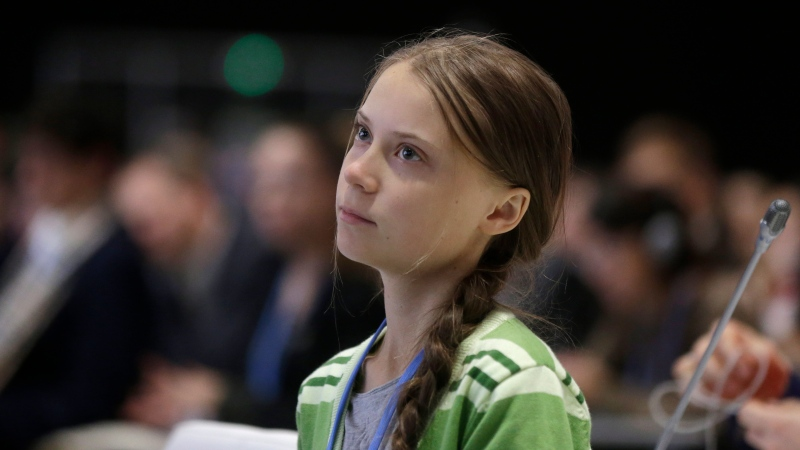 In this Wednesday, Dec. 11, 2019, file photo, Swedish climate activist Greta Thunberg listens to speeches before addressing the UN climate conference n Madrid, Spain. (AP Photo/Paul White)