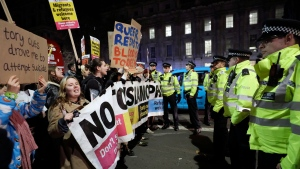 People attend an anti-Boris Johnson demonstration, in central London, Friday Dec. 13, 2019. Boris Johnson's gamble on early elections paid off as voters gave the UK prime minister a commanding majority to take the country out of the European Union by the end of January, a decisive result after more than three years of stalemate over Brexit. (AP Photo/Kirsty Wigglesworth)