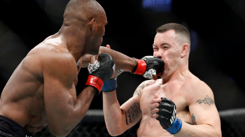 Kamaru Usman hits Colby Covington in a mixed martial arts welterweight championship bout at UFC 245, Saturday, Dec. 14, 2019, in Las Vegas. (AP Photo/John Locher)