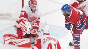 Detroit Red Wings goaltender Jonathan Bernier makes a save against Montreal Canadiens' Nate Thompson as Red Wings' Luke Glendening defends during third period NHL hockey action in Montreal, Saturday, December 14, 2019. THE CANADIAN PRESS/Graham Hughes