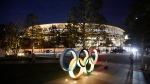 The Olympic rings stand near the new National Stadium Sunday, Dec. 15, 2019, in Tokyo. (AP Photo/Jae C. Hong)