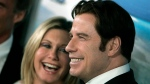 In this 2008 file photo, Olivia Newton-John, left, and John Travolta pose for photographs during arrivals to the Australia.com Black Tie Gala, at Hollywood & Highland in Los Angeles. (AP Photo/Ann Johansson)