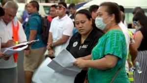 In this image from video, people gather outside a health emergency operation center Thursday, Dec. 5, 2019, in Apia, Samoa. (TVNZ via AP)