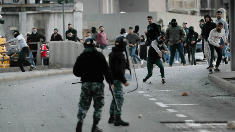Supporters of the Shiite Hezbollah and Amal Movement groups, both supporting the current government, throw stones at riot policemen, as they try to attack anti-government protesters in downtown Beirut, Lebanon, Saturday, Dec. 14, 2019. T (AP Photo/Hussein Malla)