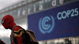 A man dressed in a Spiderman costume walks outside of the COP25 climate talks congress in Madrid, Spain, Saturday, Dec. 14, 2019. The United Nations Secretary-General has warned that failure to tackle global warming could result in economic disaster. (AP Photo/Manu Fernandez)