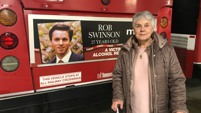 Carolyn Swinson stands next to the bus with her son, Rob's, poster on the back. (Nick Dixon/CTV News Toronto)