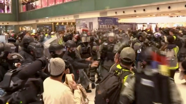 In this image made from video, police and protester scuffle at a shopping mall in Sha Tin district in Hong Kong, with shoppers watch from balconies above, Sunday, Dec. 15, 2019. (AP Photo)