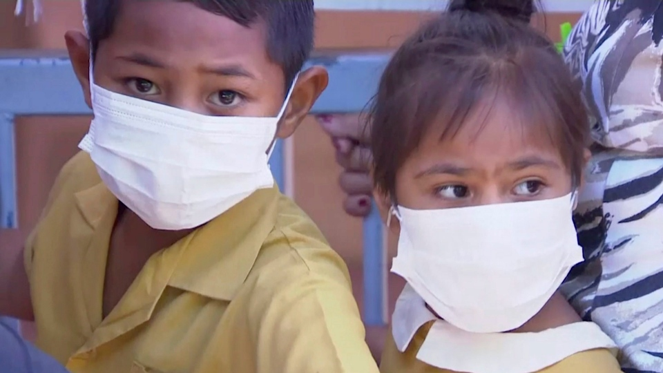 In this November 2019, image from video, masked children wait to get vaccinated at a health clinic in Apia, Samoa. (TVNZ via AP)