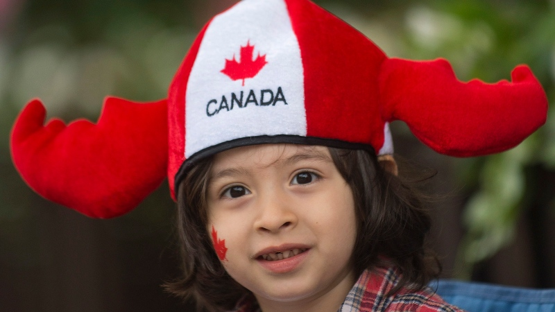 A young boy smiles as he watches the annual Canada Day parade in Montreal, Monday, July 1, 2013. (Graham Hughes / THE CANADIAN PRESS)