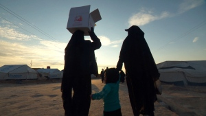 Two women and a child walk down a road in the al-Hol camp in northeastern Syria.