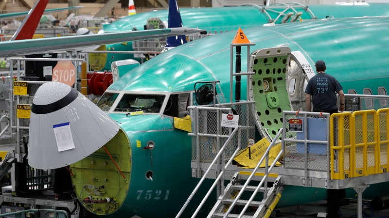 In this March 27, 2019, file photo, a worker enters a Boeing 737 MAX 8 airplane during a brief media tour of Boeing's 737 assembly facility in Renton, Wash. (AP Photo/Ted S. Warren, File)