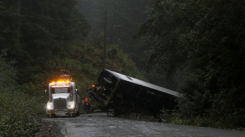 A police crash reconstruction says a bus loaded with University of Victoria students moved over for an oncoming vehicle just as a logging road narrowed before the rollover that killed two students. A tow-truck crew removes a bus from an embankment next to a logging road near Bamfield, B.C., Saturday, Sept. 14, 2019. (THE CANADIAN PRESS/Chad Hipolito)