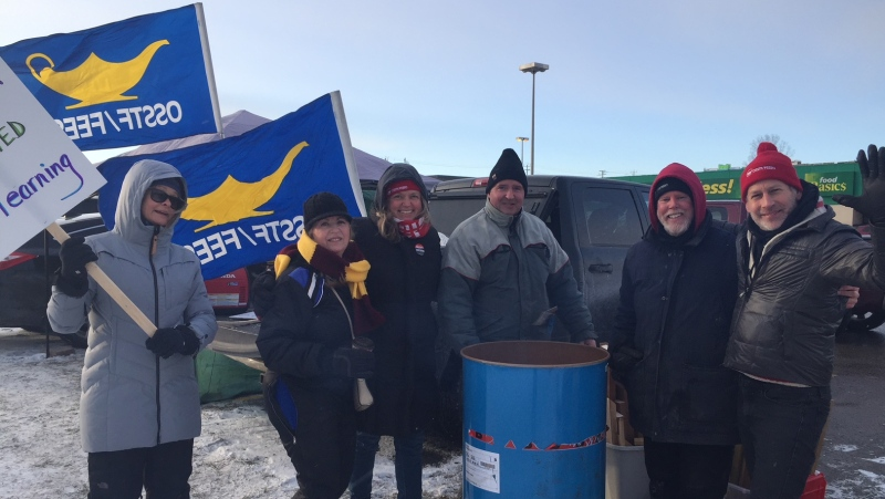 High school teachers try to stay warm as they picket in London, Ont. on Wednesday, Dec. 18, 2019. (Reta Ismail / CTV London)